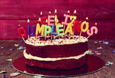 Feliz cumpleanos, happy birthday in Spanish. A cake topped with some lit letter-shaped candles forming the text feliz cumpleanos, happy birthday in Spanish stock photos