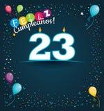 Feliz Cumpleanos 23 - lycklig födelsedag 23 i spanskt språk - hälsningkort med vita stearinljus Arkivbilder