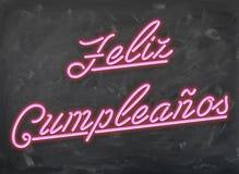 Feliz Cumpleanos - rosa Neonguß auf handwiped dunklem Kreide-Brett stockfotos