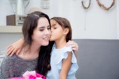 feliz de asiático de la madre y de la hija con el regalo con la cinta rosada y la hija que besa a la madre Fotos de archivo libres de regalías
