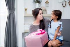 feliz de asiático de la madre y de la hija con el regalo con la cinta rosada y la hija que besa a la madre Imagen de archivo