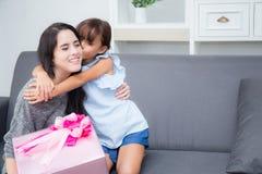 feliz de asiático de la madre y de la hija con el regalo con la madre rosada del beso de la cinta y de la hija Foto de archivo libre de regalías