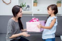 feliz de asiático de la madre y de la hija con el regalo con la cinta rosada Imágenes de archivo libres de regalías