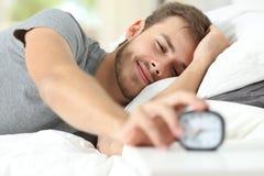 Feliz despierte de un hombre feliz que para el despertador Fotografía de archivo libre de regalías