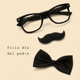 Feliz dia del padre, happy fathers day written in spanish. Sentence feliz dia del padre, happy fathers day written in spanish, and glasses, mustache and bow tie royalty free stock images