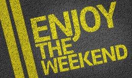 Feliz disfrute del fin de semana escrito en el camino Fotos de archivo libres de regalías