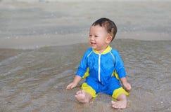 Feliz do bebê asiático no terno de natação que senta-se na praia da areia fotografia de stock