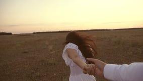 feliz em corridas dos pares do amor em conjunto Corridas da menina atrav?s do campo que guarda a m?o de seus homem e risos amados video estoque