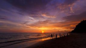 Feliz en la playa en puesta del sol Fotos de archivo