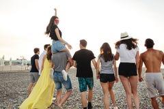 Feliz equipa e a caminhada da mulher no grupo de praia de amigos que apreciam feriados da praia foto de stock