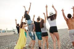 Feliz equipa e a caminhada da mulher no grupo de praia de amigos que apreciam feriados da praia fotografia de stock