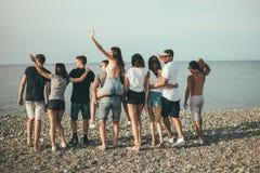 Feliz equipa e a caminhada da mulher no grupo de praia de amigos que apreciam feriados da praia imagens de stock