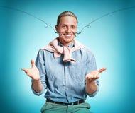 Feliz excite al hombre joven que sonríe sobre fondo azul foto de archivo libre de regalías
