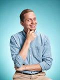 Feliz excite o homem novo que sorri sobre o fundo azul imagem de stock royalty free