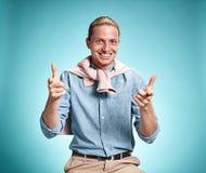 Feliz excite o homem novo que sorri sobre o fundo azul fotografia de stock