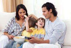 Feliz familia que ve la TV en el sofá Fotografía de archivo libre de regalías