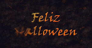 Feliz Halloween text in Spanish dissolving into dust to left Stock Image