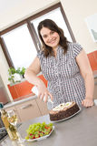 Feliz mais a mulher do tamanho com bolo de chocolate Foto de Stock