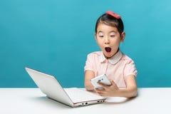 Feliz, a menina de Ásia está sentando-se na tabela com seu lapto branco Fotografia de Stock Royalty Free