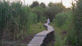 Feliz muchacha activa del niño en los funcionamientos blancos del vestido a lo largo del puente de madera en naturaleza entre alt almacen de video