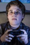 Feliz. muchacho con la palanca de mando que juega al juego de ordenador en casa. Foto de archivo