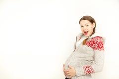 Feliz, mujer embarazada de los jóvenes en una ropa del invierno en un fondo blanco Imagen de archivo