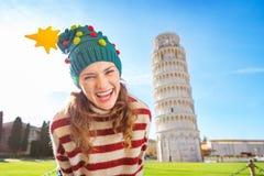 Feliz mujer en el viaje que se inclina cercano del sombrero del árbol de navidad de Pisa Imagen de archivo libre de regalías
