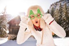 Feliz mujer en vidrios de una Navidad delante de una casa de la montaña Imagen de archivo libre de regalías