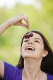 Feliz mujer joven que come cerezas Imágenes de archivo libres de regalías