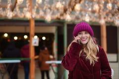 Feliz mujer joven que habla en el teléfono móvil en el fondo Imagenes de archivo