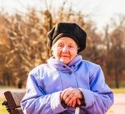 Feliz mujer mayor que se sienta en un banco con un palillo Fotos de archivo