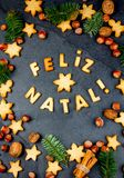 FELIZ NATAL COOKIES. Words Merry Christmas en portuguese with baked cookies, Christmas decoration and nuts on black. Slate background. Christmas card for Stock Image