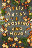 FELIZ NATAL COOKIES. Words Merry Christmas and Happy New Year en portuguese with baked cookies, Christmas decoration and. Nuts on black slate background Royalty Free Stock Photo