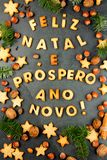 FELIZ NATAL COOKIES. Words Merry Christmas and Happy New Year en portuguese with baked cookies, Christmas decoration and. Nuts on black slate background Stock Images