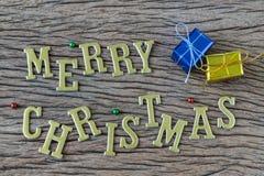 Feliz Natal dourado dos alfabetos com a caixa atual colorida no wo Foto de Stock