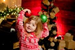 Feliz Natal e ano novo feliz Árvore de Natal bonito das bolas dos ornamento do jogo da menina da criança pequena A criança apreci imagens de stock