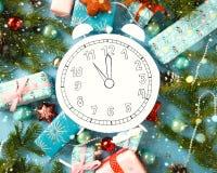 Feliz Natal e ano novo feliz Cronometre, cortado do papel, cercado por ramos do abeto e por presentes Imagens de Stock
