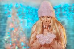 Feliz Natal e ano novo feliz! menina de sorriso bonita feliz no chapéu e em mitenes feitos malha que fica exterior e que guarda a foto de stock
