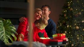 Feliz Natal e boas festas crianças alegres e pais bonitos que abrem presentes Pijamas vestindo do menino que têm o divertimento p video estoque