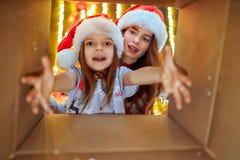 Feliz Natal e boas festas mamã alegre e sua menina bonito da filha que abrem um presente de Natal Pai e imagens de stock royalty free