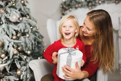 Feliz Natal e boas festas Mamã alegre e sua menina bonito da filha que trocam presentes fotos de stock