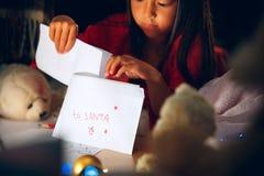 Feliz Natal e boas festas A menina bonito da criança pequena escreve a letra a Santa Claus perto da árvore de Natal fotografia de stock royalty free
