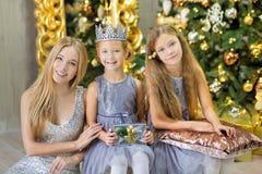 Feliz Natal e boas festas meninas bonitos da criança pequena que decoram a árvore de Natal verde branca dentro com muitos present fotografia de stock