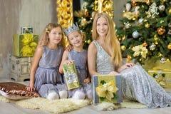 Feliz Natal e boas festas meninas bonitos da criança pequena que decoram a árvore de Natal verde branca dentro com muitos present imagens de stock