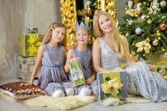 Feliz Natal e boas festas meninas bonitos da criança pequena que decoram a árvore de Natal verde branca dentro com muitos present foto de stock