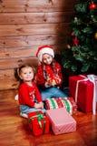 Feliz Natal e feriado feliz Duas meninas bonitos da criança pequena com as caixas de presente atuais perto da árvore interna imagens de stock