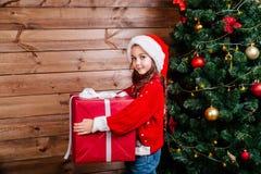 Feliz Natal e feriado feliz Menina bonito da criança pequena com a caixa de presente atual vermelha grande perto da árvore intern foto de stock