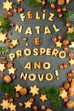 FELIZ NATAL-KOEKJES Woorden Vrolijke Kerstmis en Gelukkig Nieuwjaar het Engelse Portugees met gebakken koekjes, Kerstmisdecoratie Stock Afbeeldingen