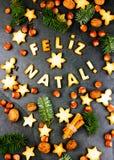 FELIZ NATAL-KOEKJES Woorden Vrolijke Kerstmis het Engelse Portugees met gebakken koekjes, Kerstmisdecoratie en noten op zwarte Stock Fotografie