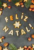 FELIZ NATAL-KOEKJES Woorden Vrolijke Kerstmis het Engelse Portugees met gebakken koekjes, Kerstmisdecoratie en noten op zwarte Stock Afbeeldingen